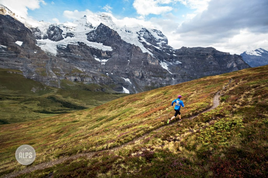 Trail running around Kleine Scheidegg in fall colors, Switzerland. The Jungfrau Group is in the background, the Eiger, Mönch and Jungfrau.