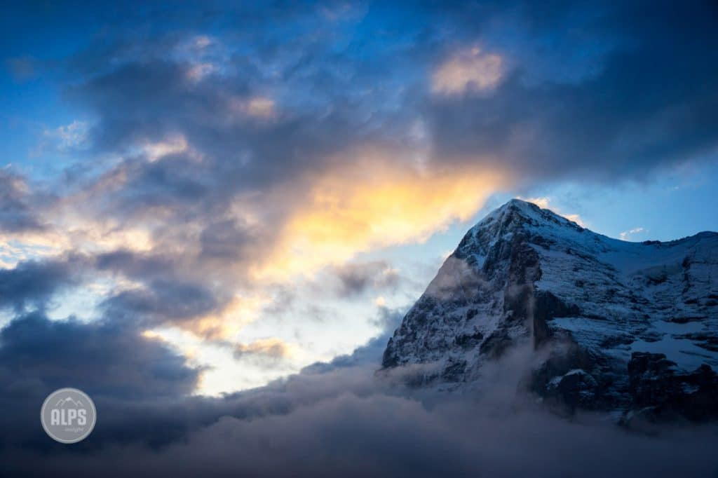 The Eiger at sunrise from Kleine Scheidegg, surrounded in clouds from a clearing overnight storm. Grindelwald, Switzerland