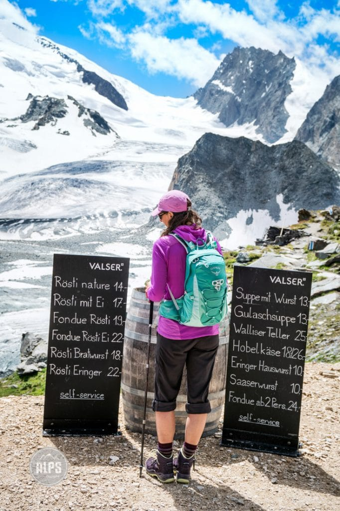 A hiker stands on the Brittania Hut deck looking at the menu sign. Saas Fee, Switzerland