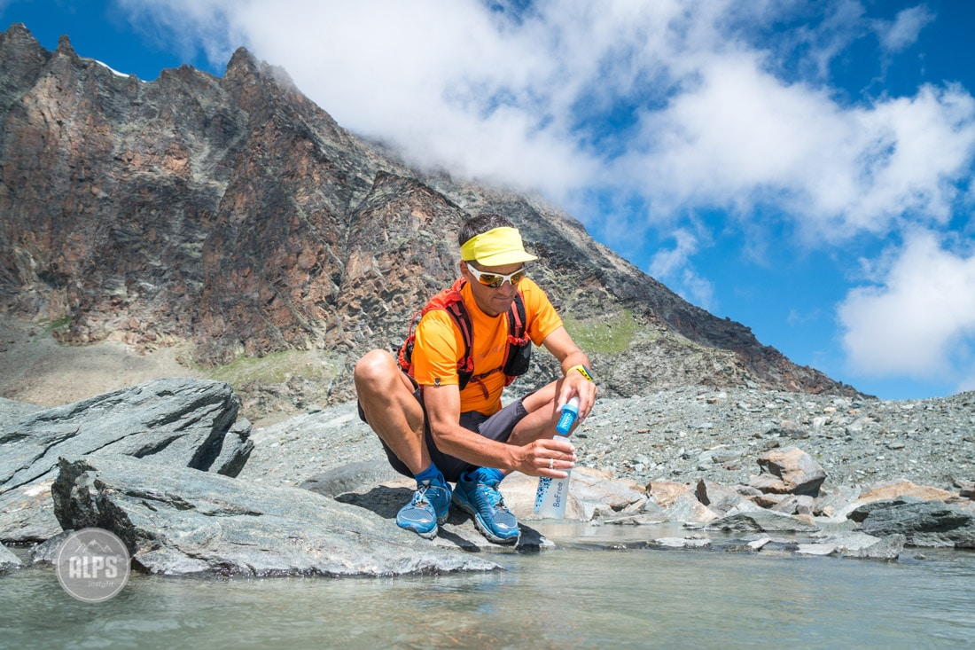 A trail runner sits by a small creek filling his waterbottle, that uses a Katadyn BeFree filter system.