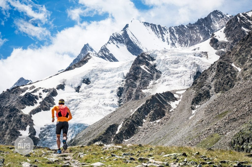 A trail runner on perfect singletrack above Saas Fee, Switzerland with the Mischabel Group in the background