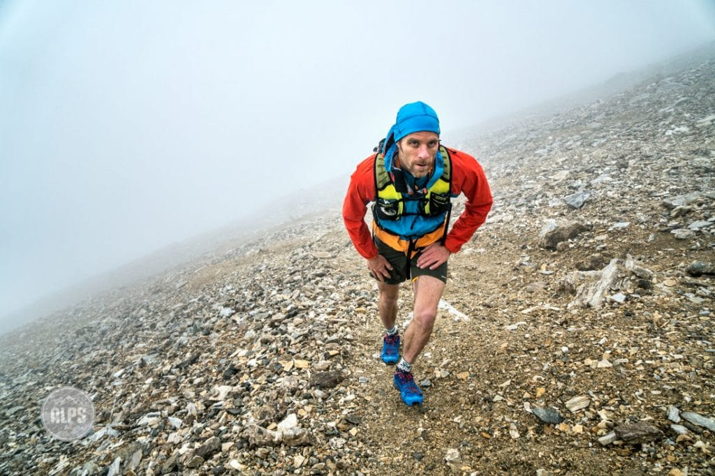 A trail runner in foggy weather heading for the Barrhorn (3610 meters), the highest peak in Switzerland that has a trail to the top. Turtmenntal, Switzerland