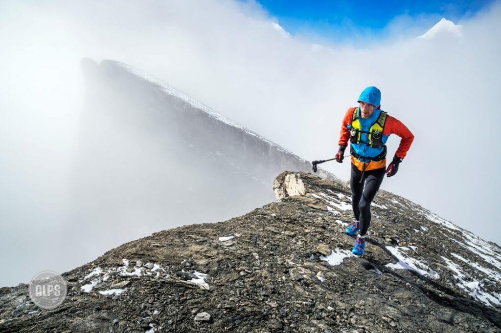 A trail runner arriving to the summit after climbing the Üssers Barrhorn (3610 meters), the highest peak in Switzerland that has a trail to the top. Turtmenntal, Switzerland