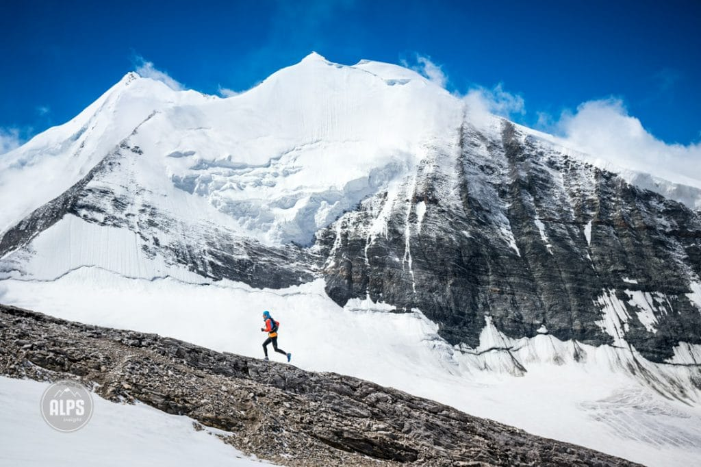 A trail runner climbing the Üssers Barrhorn (3610 meters), the highest peak in Switzerland that has a trail to the top. Turtmenntal, Switzerland. in the background is the Weisshorn and Bishorn in clearing clouds.