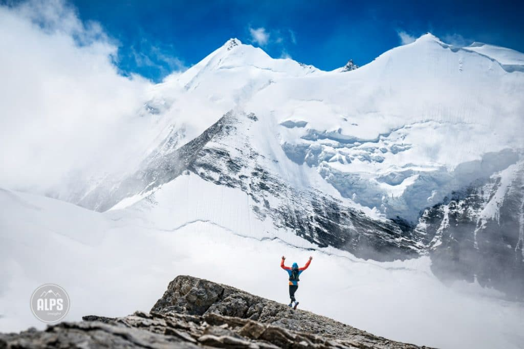 A trail runner raising his hands in joy while on his way down after climbing the Barrhorn (3610 meters), the highest peak in Switzerland that has a trail to the top. Turtmenntal, Switzerland. in the background is the Weisshorn and Bishorn in clearing clouds.