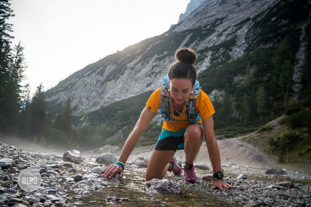 A trail runner stops to put her knee in cold water after injuring it while running.