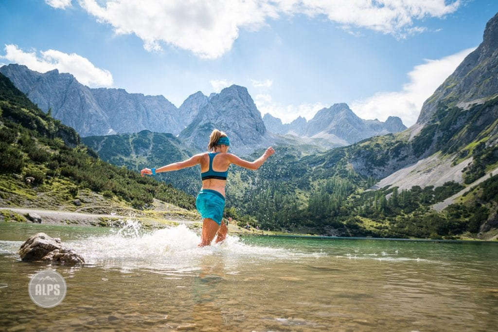 A trail runner stops to swim in a mountain lake, near the Zugspitze, Germany