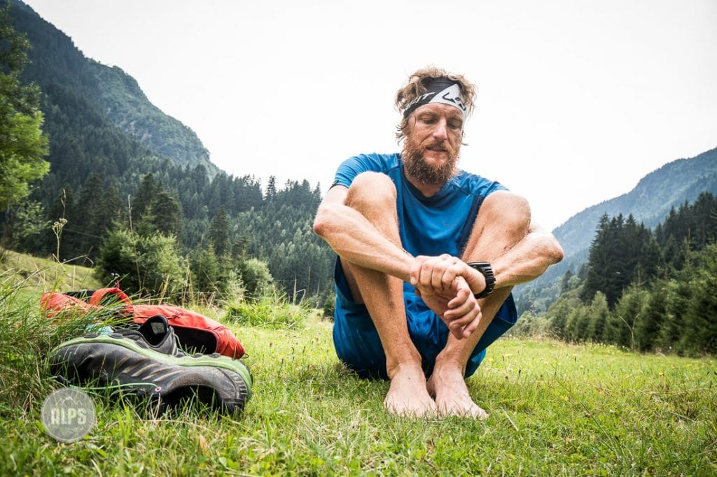 A trail runner sits with his shoes off looking fatigued and tired after a full day running through Austria