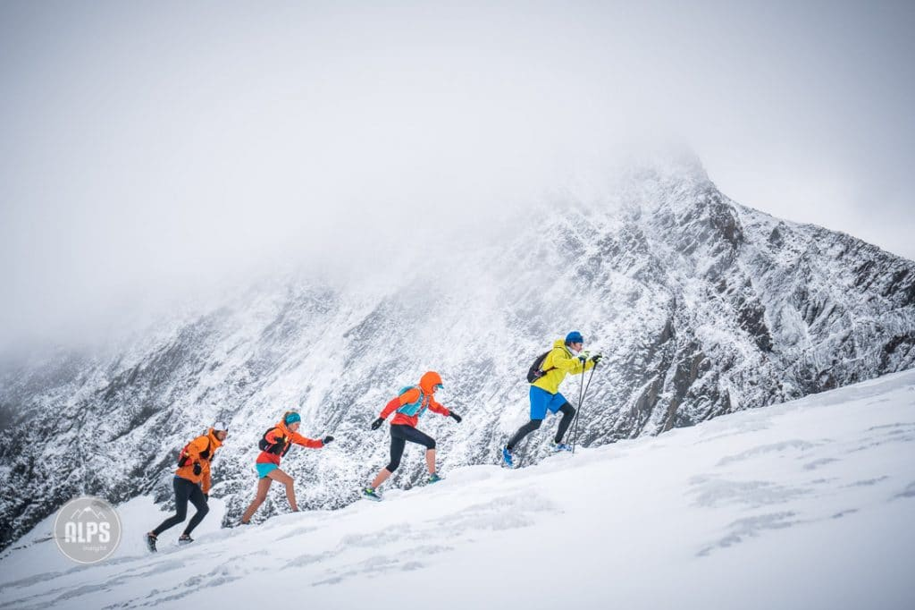 Trail runners passing the high mountains of the Stubai with fresh snow during a multi-day trail running tour through Austria