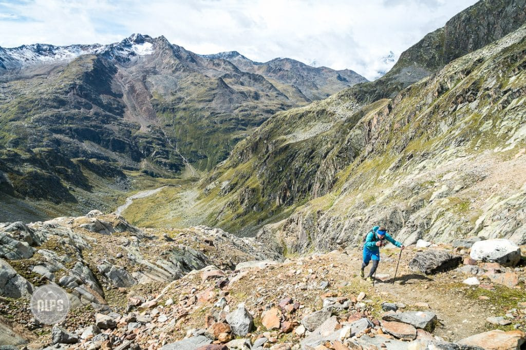 A lone trail runner climbing up a long, steep trail while on a multi-day running tour through the Alps