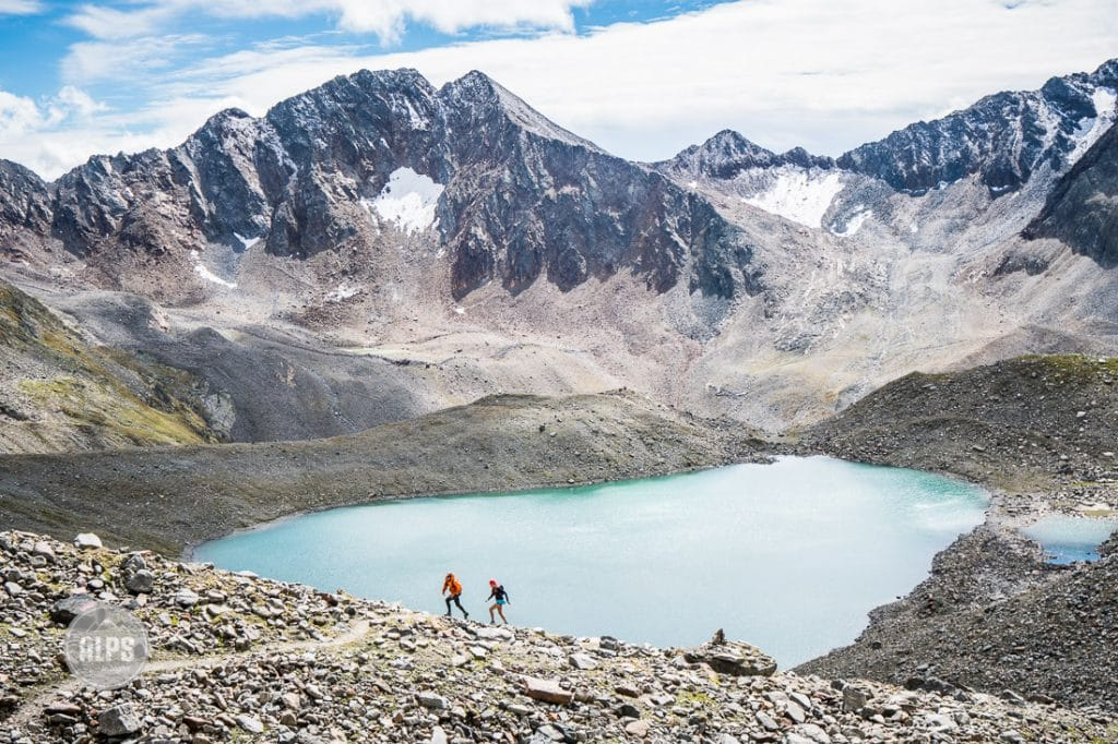 Trail runners running above a lake in the Austrian Alps