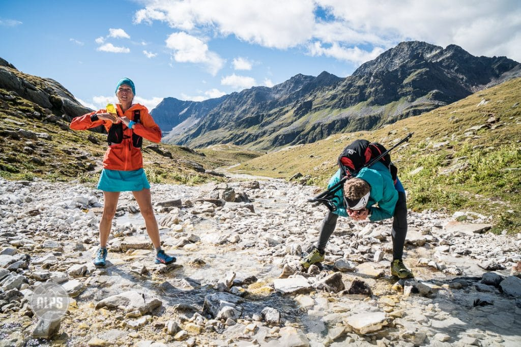 Two trail runners stopped at a mountain creek to drink and fill their water bottles, Italy.
