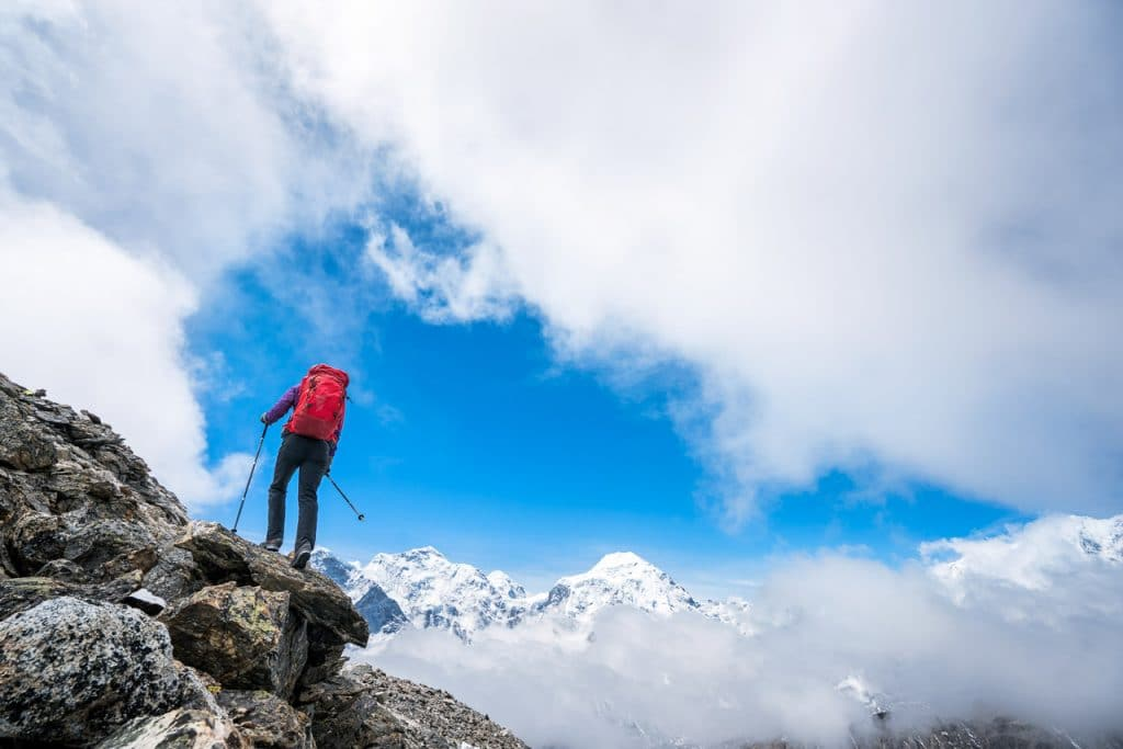A trekker hiking up rocks against a dramatic sky and clouds with distant views of big Himalayan peaks, Tibet