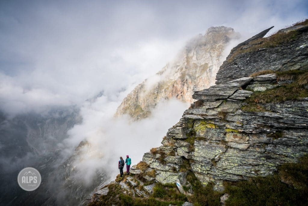 The Via Alta Verzasca is a five day ridge traverse hike above the Valle Verzasca in the Ticino region of Switzerland. Hikers approaching in thick clouds.