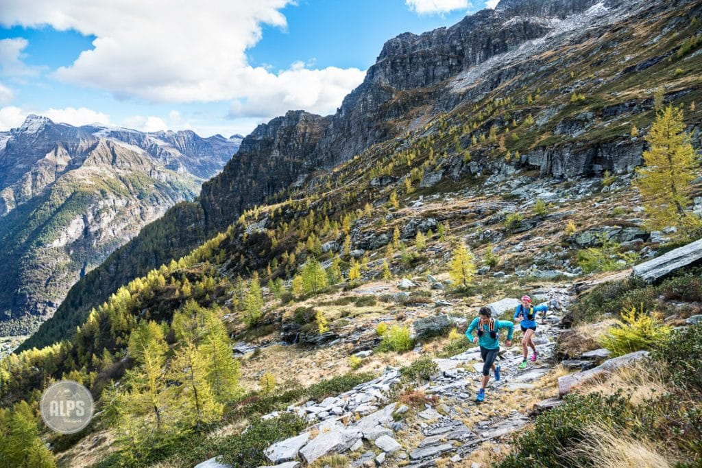 A couple trail running above Val Verzasca on the trail to Monte Zucchero, a 2735 meter summit in the Ticino region of Switzerland.