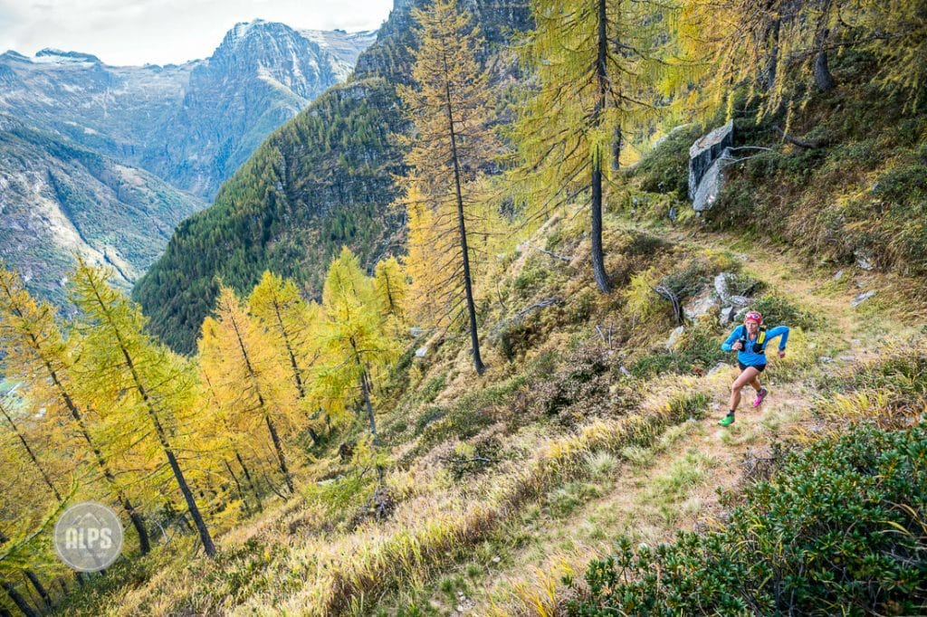 A woman trail running from the Val Verzasca on the trail to Monte Zucchero, a 2735 meter summit in the Ticino region of Switzerland.