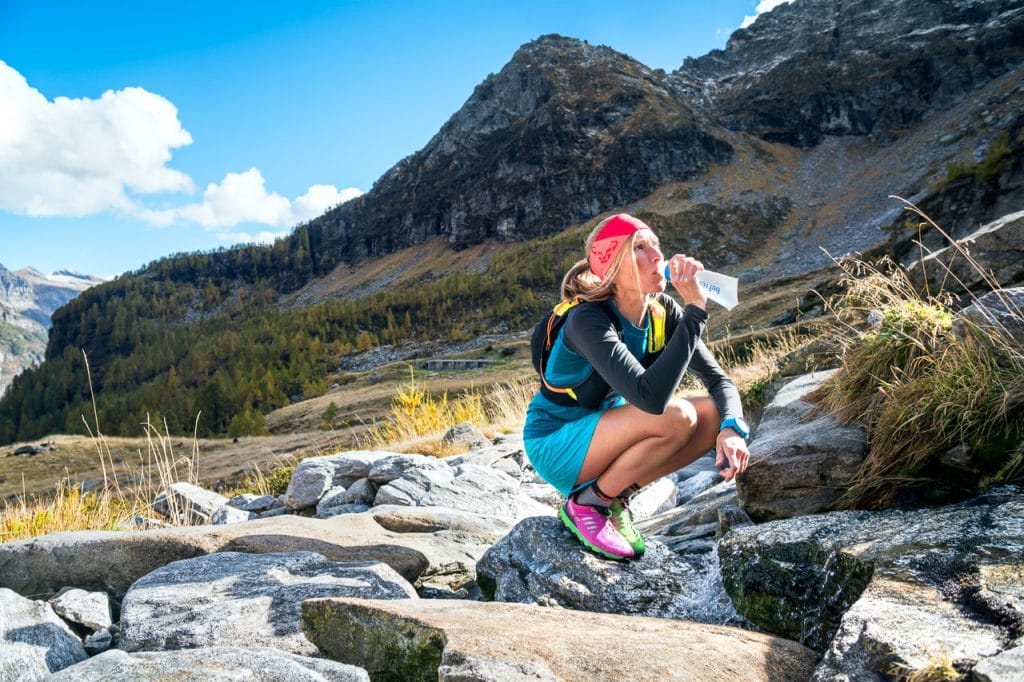 A woman trail runner stops at a mountain creek to fill her water bottle and drink. Val Verzasca, Switzerland