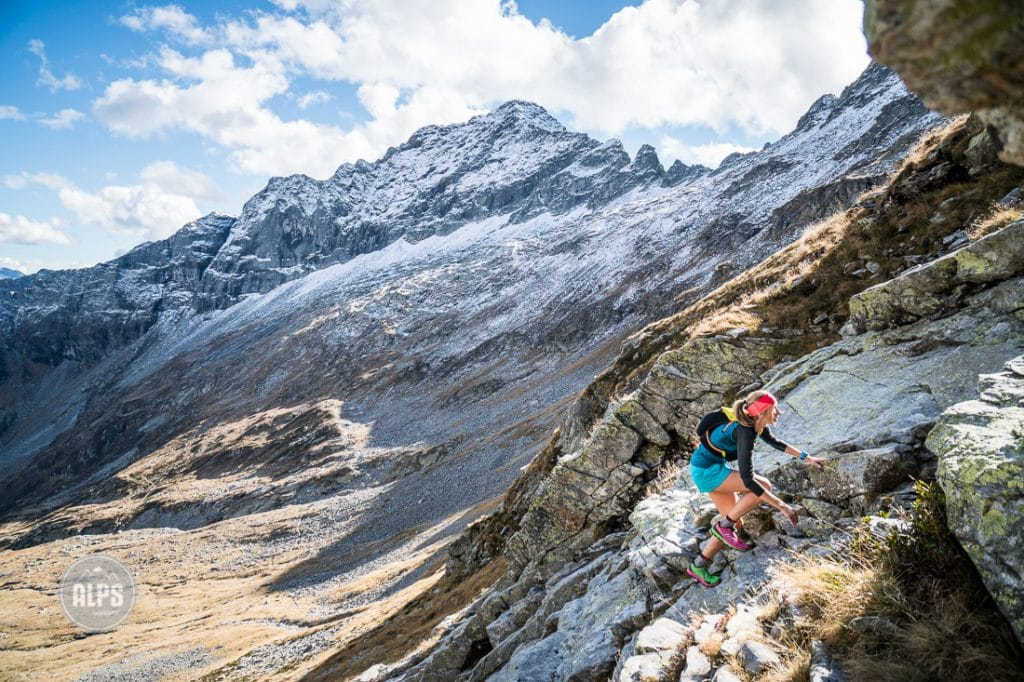A woman trail running from the Val Verzasca on the trail to Monte Zucchero, a 2735 meter summit in the Ticino region of Switzerland. arrives to a steep section with some scrambling through rocks.