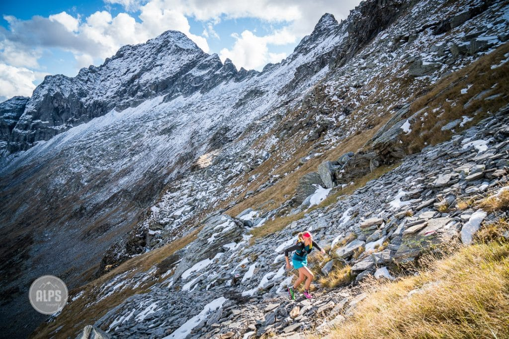 A woman trail running from Val Verzasca on the trail to Monte Zucchero, a 2735 meter summit in the Ticino region of Switzerland.