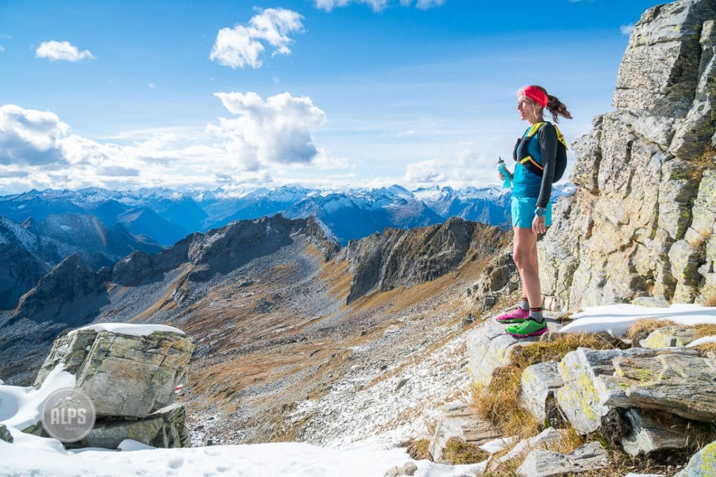 A woman trail runner stops to look at the view and drink water while on the way up Monte Zucchero, from the Val Verzasca, in the Ticino Region of Switzerland.