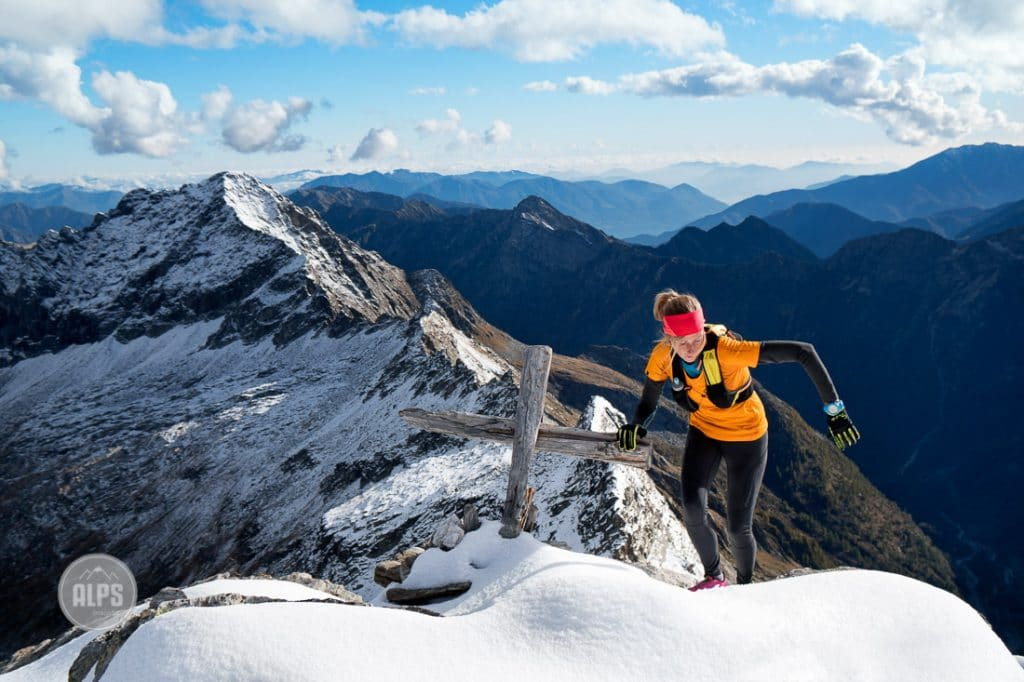 A woman trail runner on the snowy summit of Monte Zucchero, a 2735 meter summit in the Ticino Region of Switzerland from the Val Verzasca.