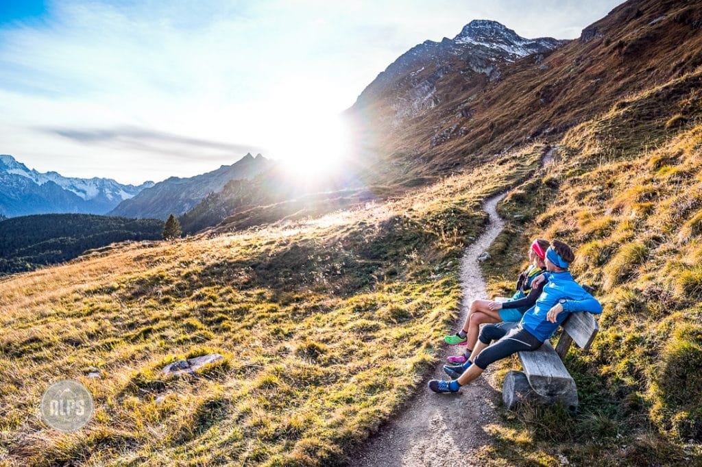 Two runners sit on a trail side bench watching the sunset after a run on the Piz Lunghin above Maloja, Switzerland