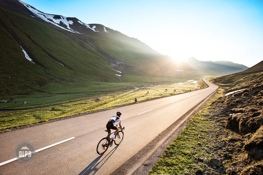 A road biker descending alone in the wide open landscape of the Albula Pass at sunrise