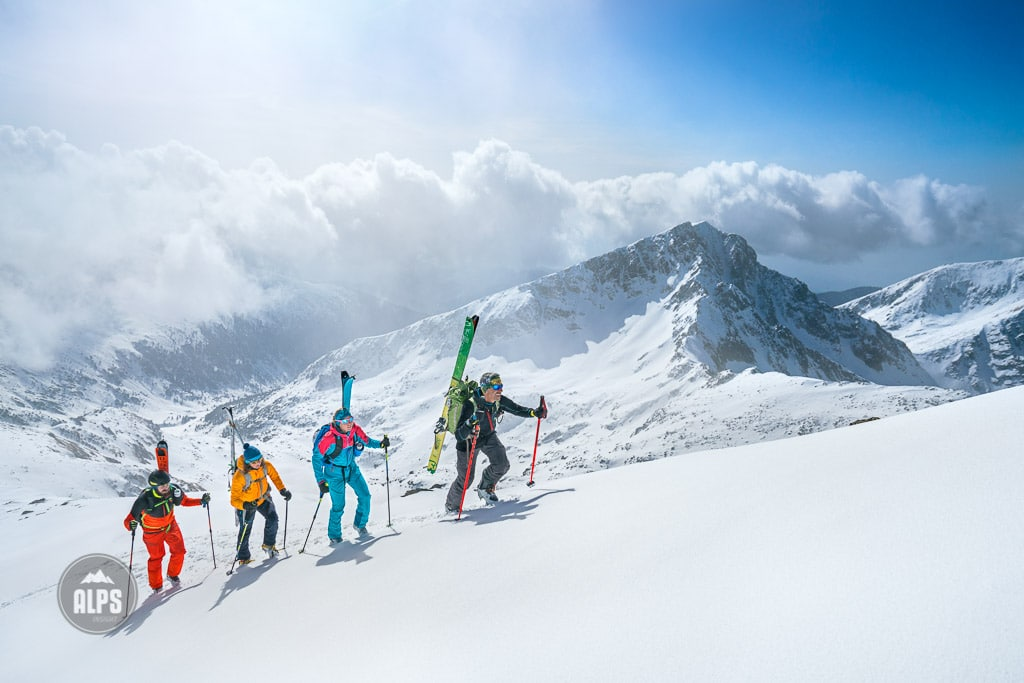 A ski tour through the Pirin Mountains of Bulgaria. Skiers carry their skis on the Kamenitsa Mountain from the Tevno Ezero Hut.