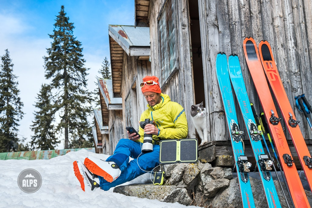 A ski tour through the Pirin Mountains of Bulgaria. Sitting outside a small cabin at the Demianica Hut, Dan Patitucci uses a solar panel to charge a battery and use a camera as a cat sits next to him.