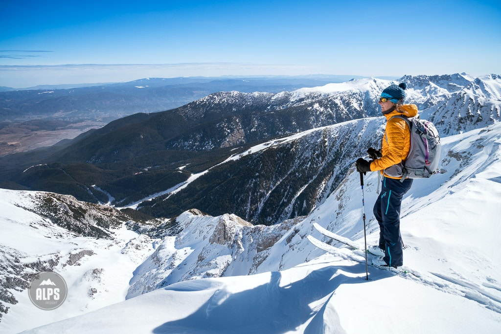 A ski tour through the Pirin Mountains of Bulgaria. A woman stands on the summit of Vihren, the highest peak of the Pirin Mounatins at 2914 meters.