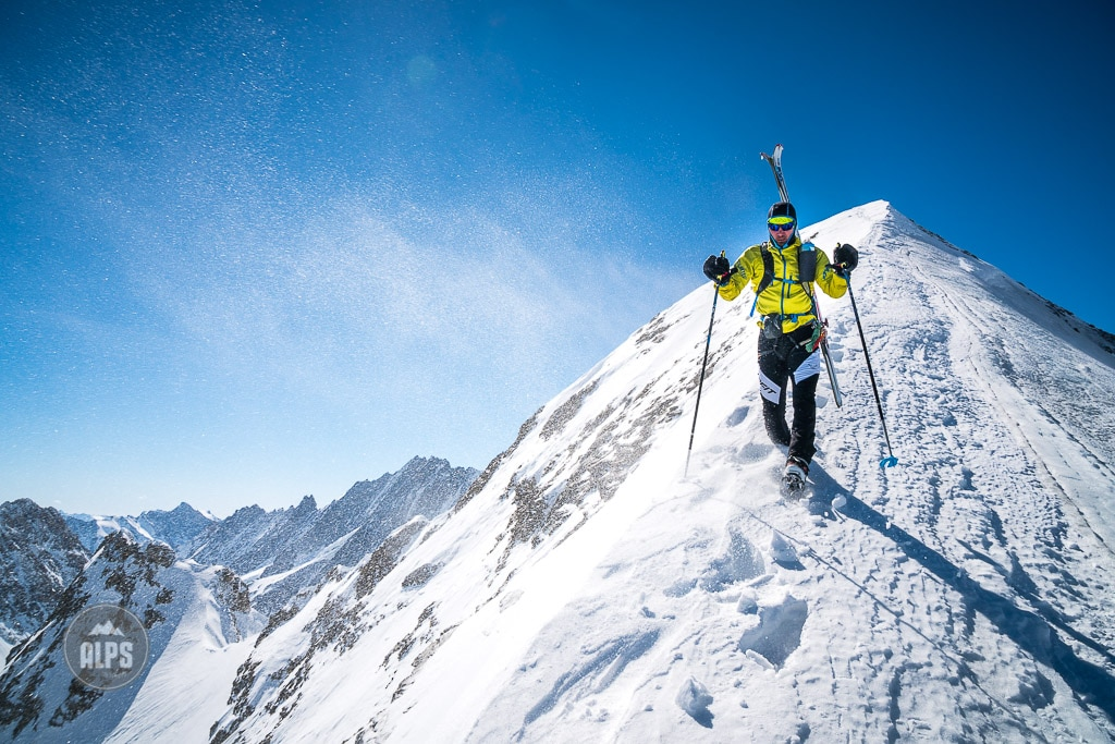 A ski mountaineer carries his skis while descending the east ridge of the Mittelhorn during a ski mountaineering tour of the Wetterhorn, Mittelhorn and Rosenhorn, in the Bernese Oberland, Switzerland