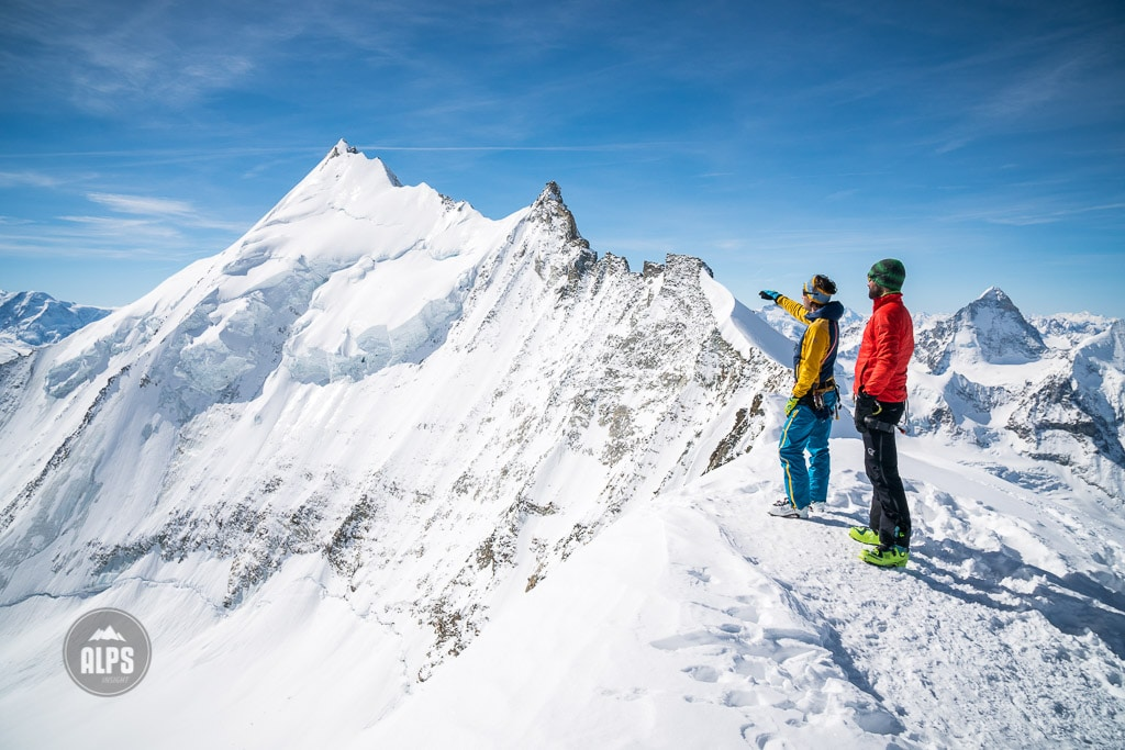 Two skiers on the summit of the Bishorn stand looking at the massive north east face of the Weisshorn. Switzerland.