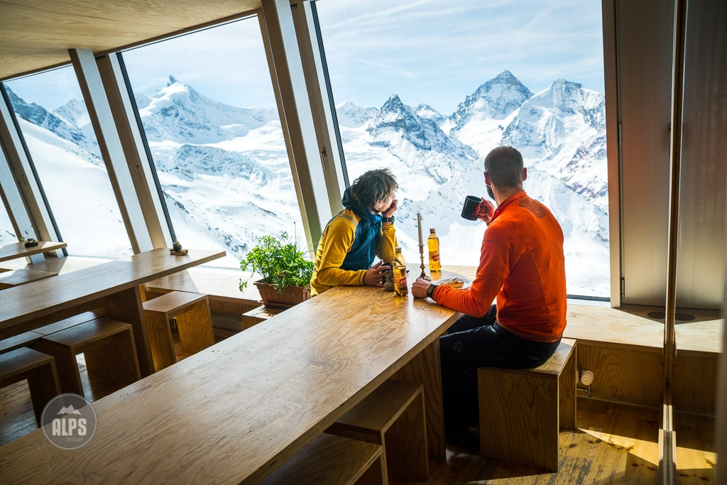 Inside the Tracuit Hut dining room, huge windows allow two visitors having coffee and tort, a panoramic view of the Swiss Alps, including the Dent Blanche. Zinal, Switzerland.